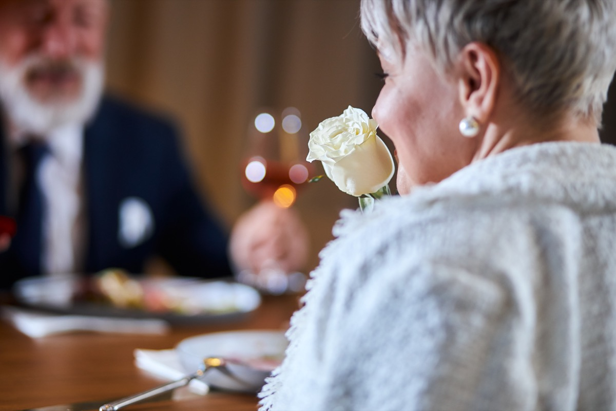 older woman smelling white rose