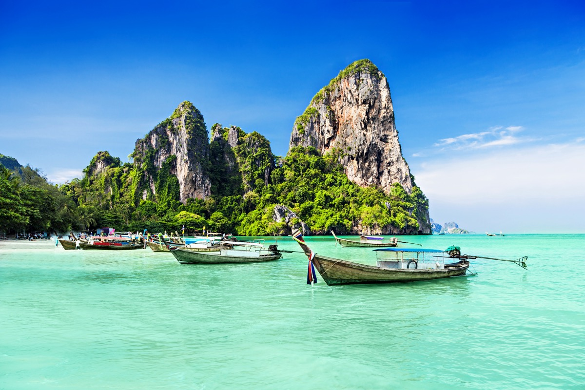 three boats in turquoise water with tropical islands