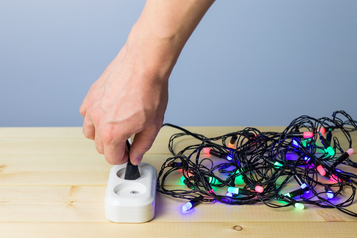 Person plugging in Christmas lights