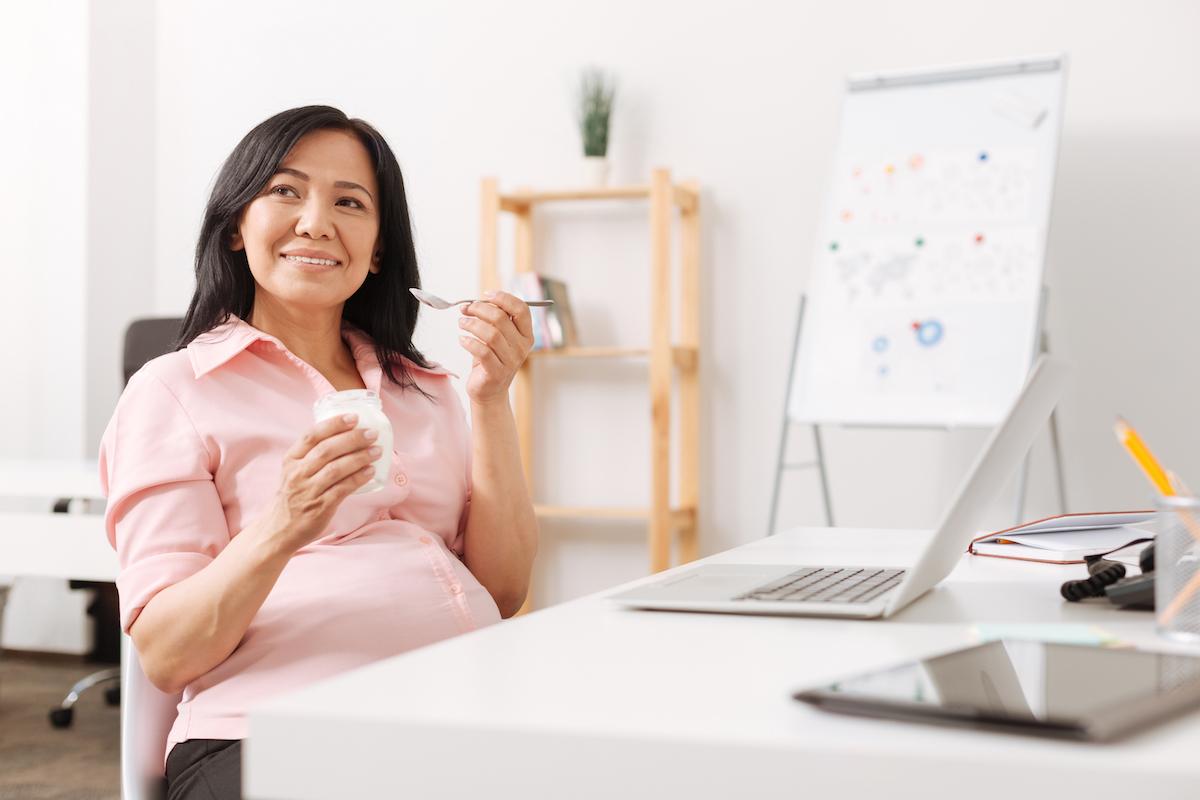 Pregnant woman eating yogurt