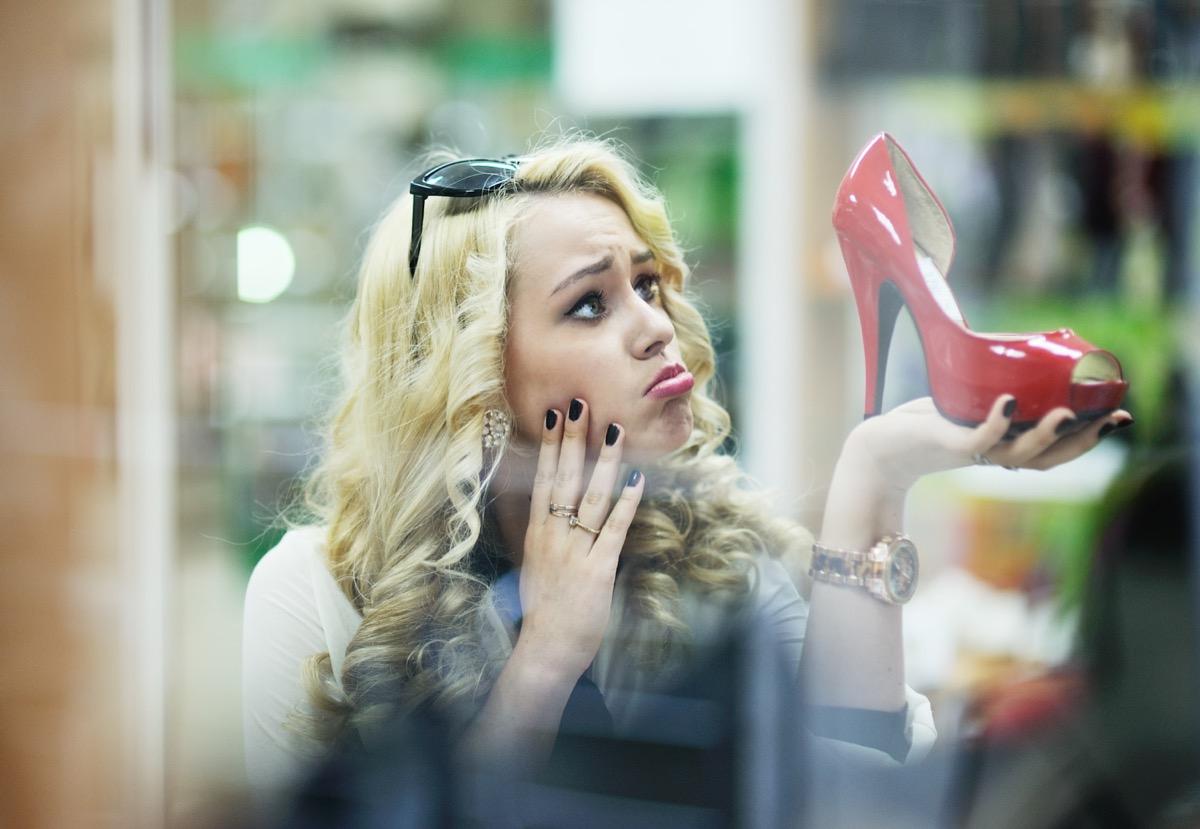 sad woman looking at a shoe