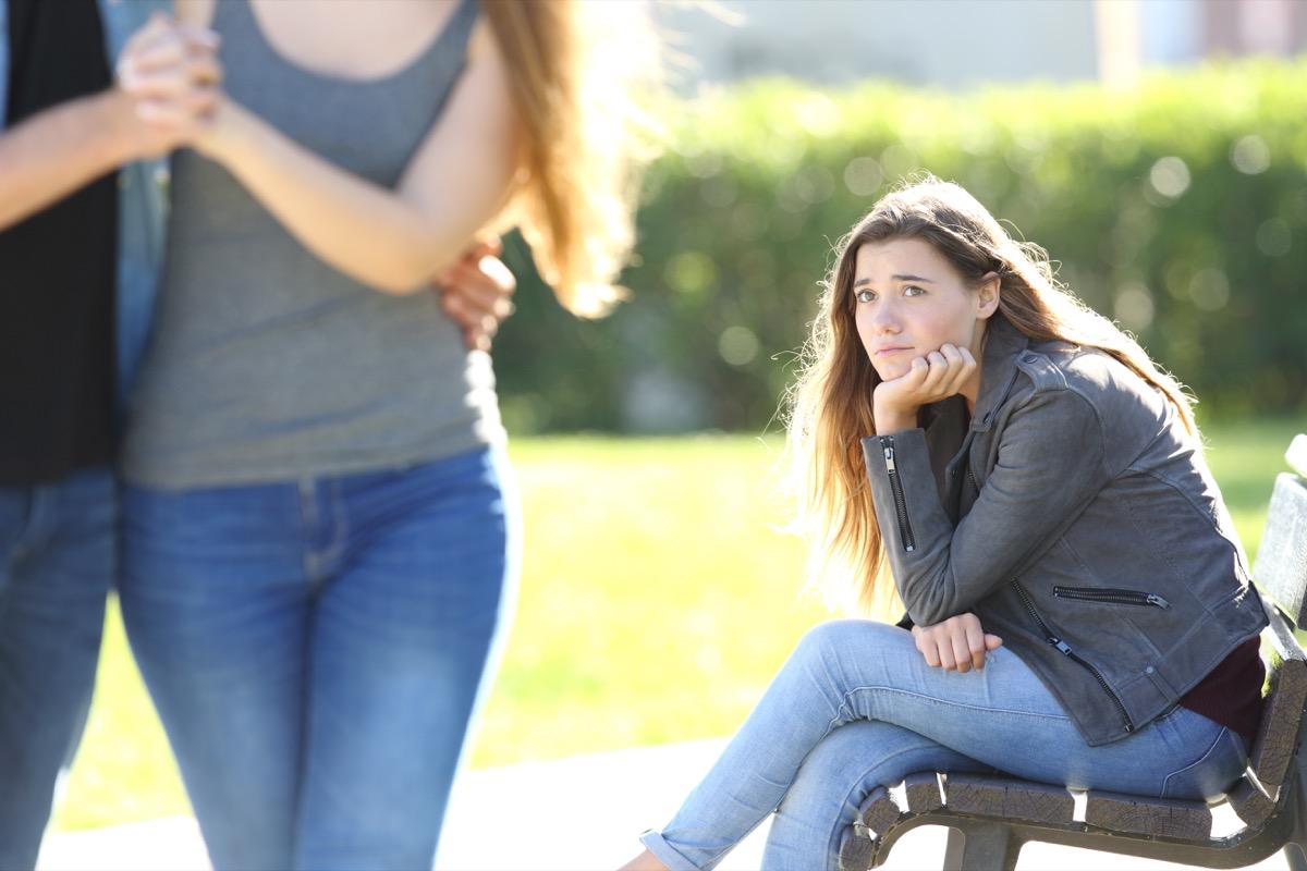 sad woman looking at couple at a park
