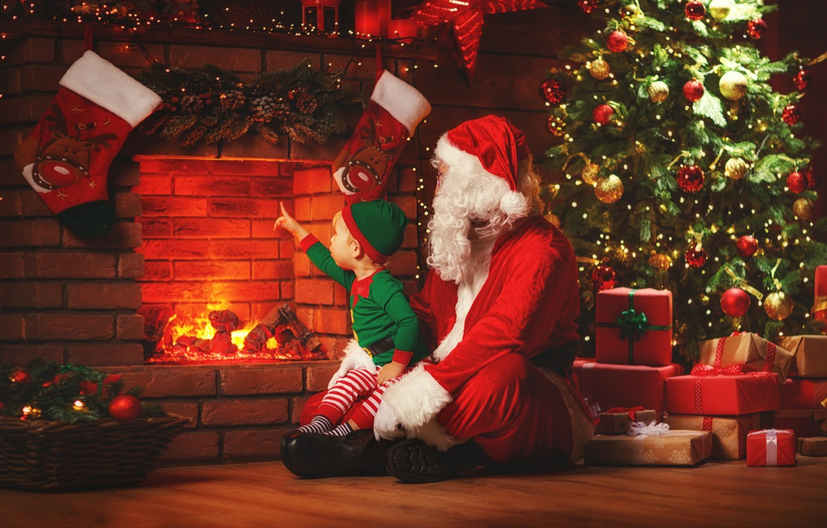 santa and elf in front of fireplace