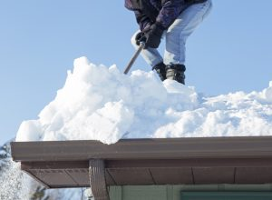man scraping snow off roof