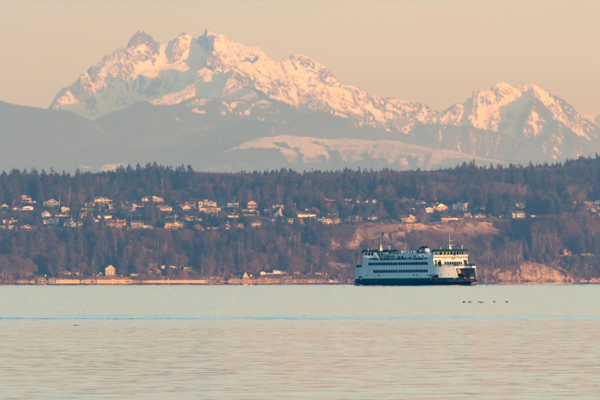 seattle ferry floats in the bay with snowy mountains behind it