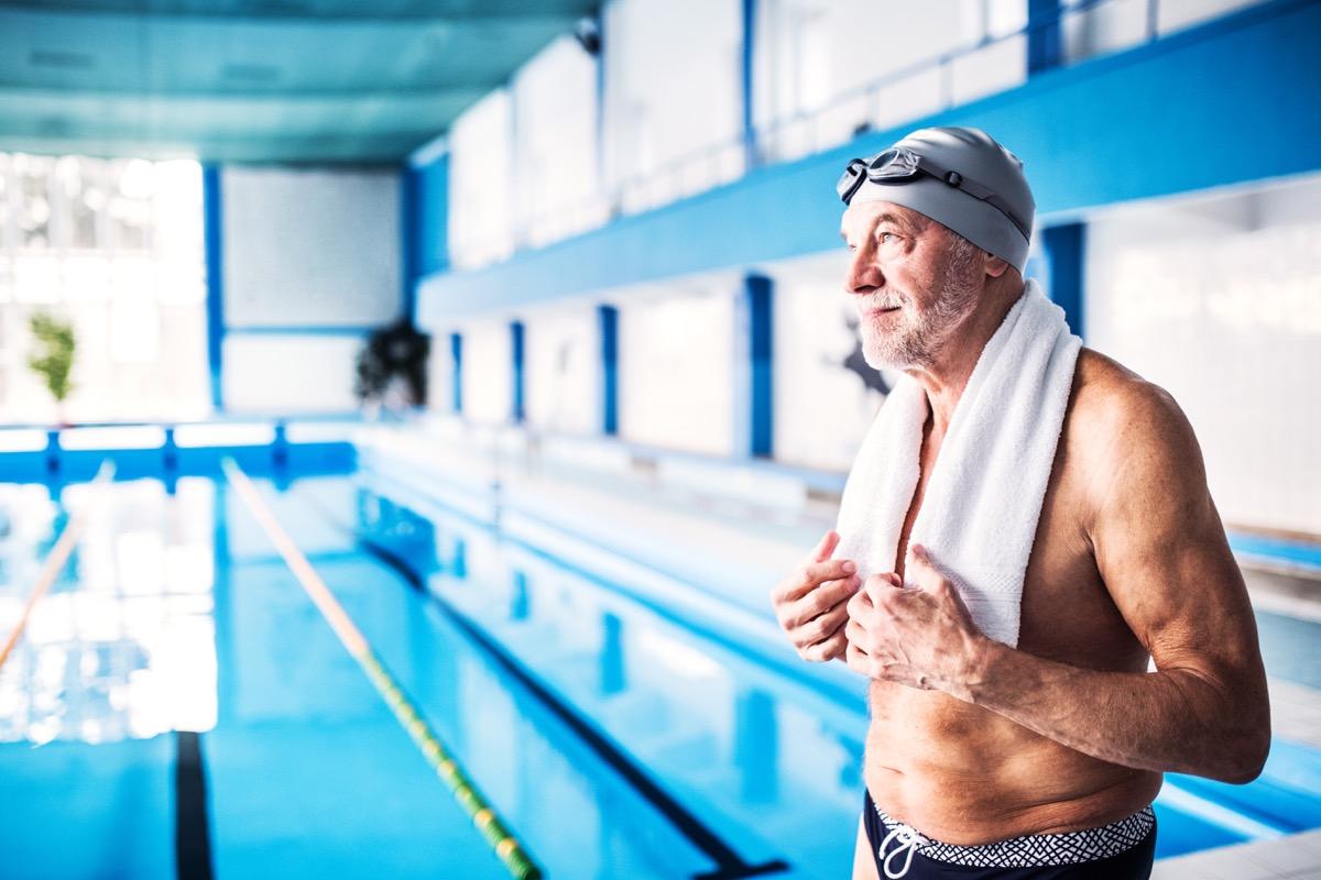 senior man standing by indoor pool