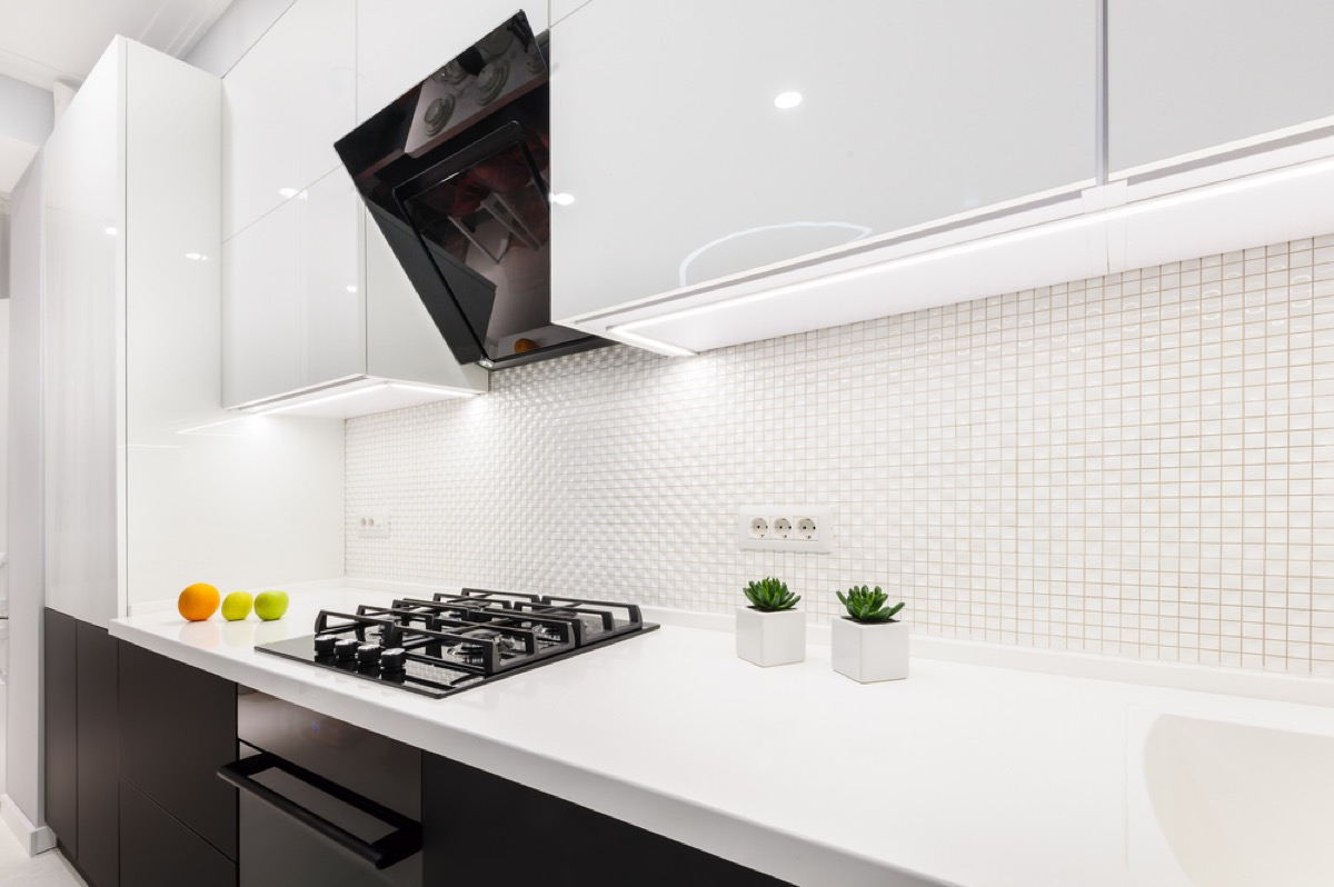 glossy white kitchen with black microwave