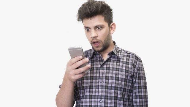 Close-up portrait of shocked young man looking at smart phone's screen receiving bad news on a white background