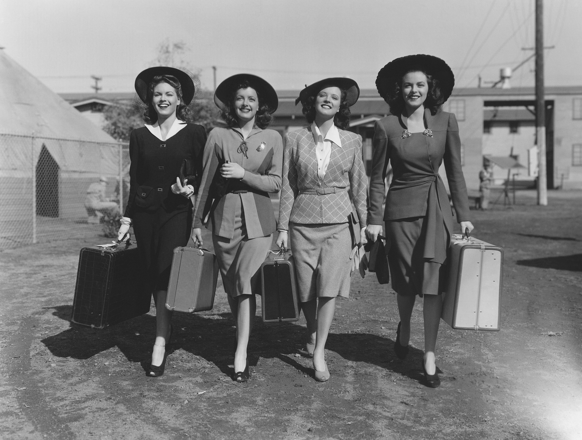 four women walk with suitcases