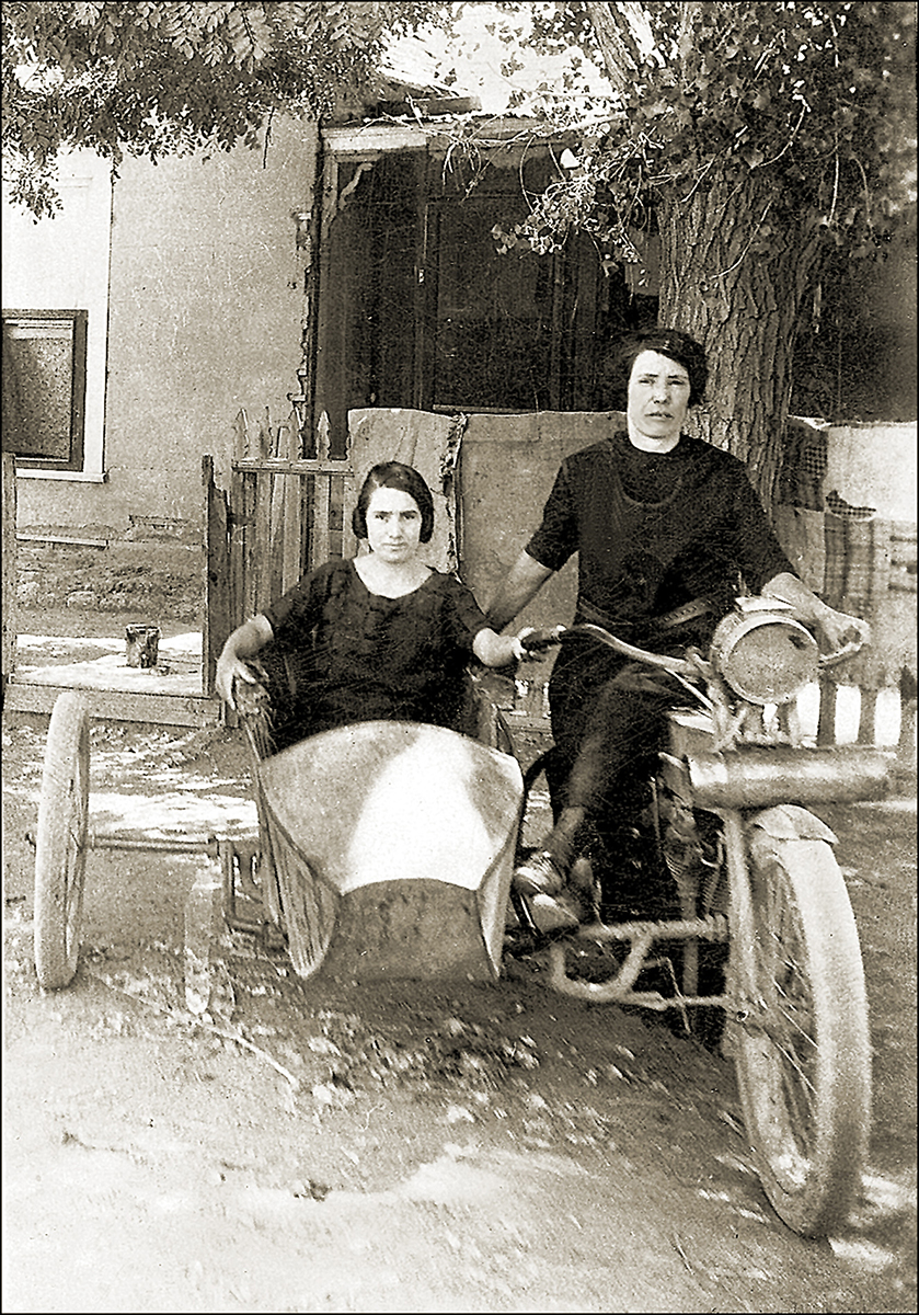 two women ride a motorcycle and sidecar