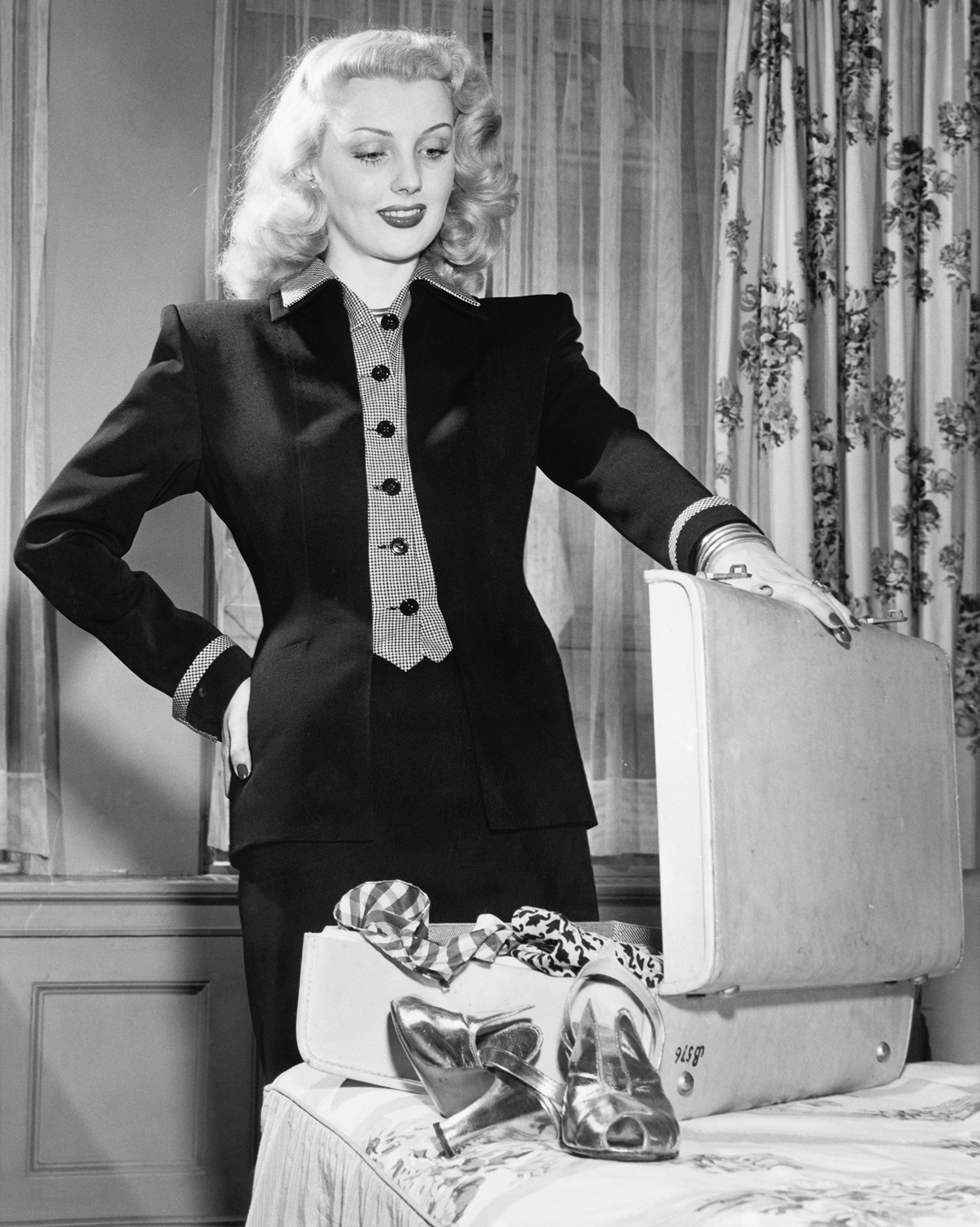 a 1940s woman opens a suitcase