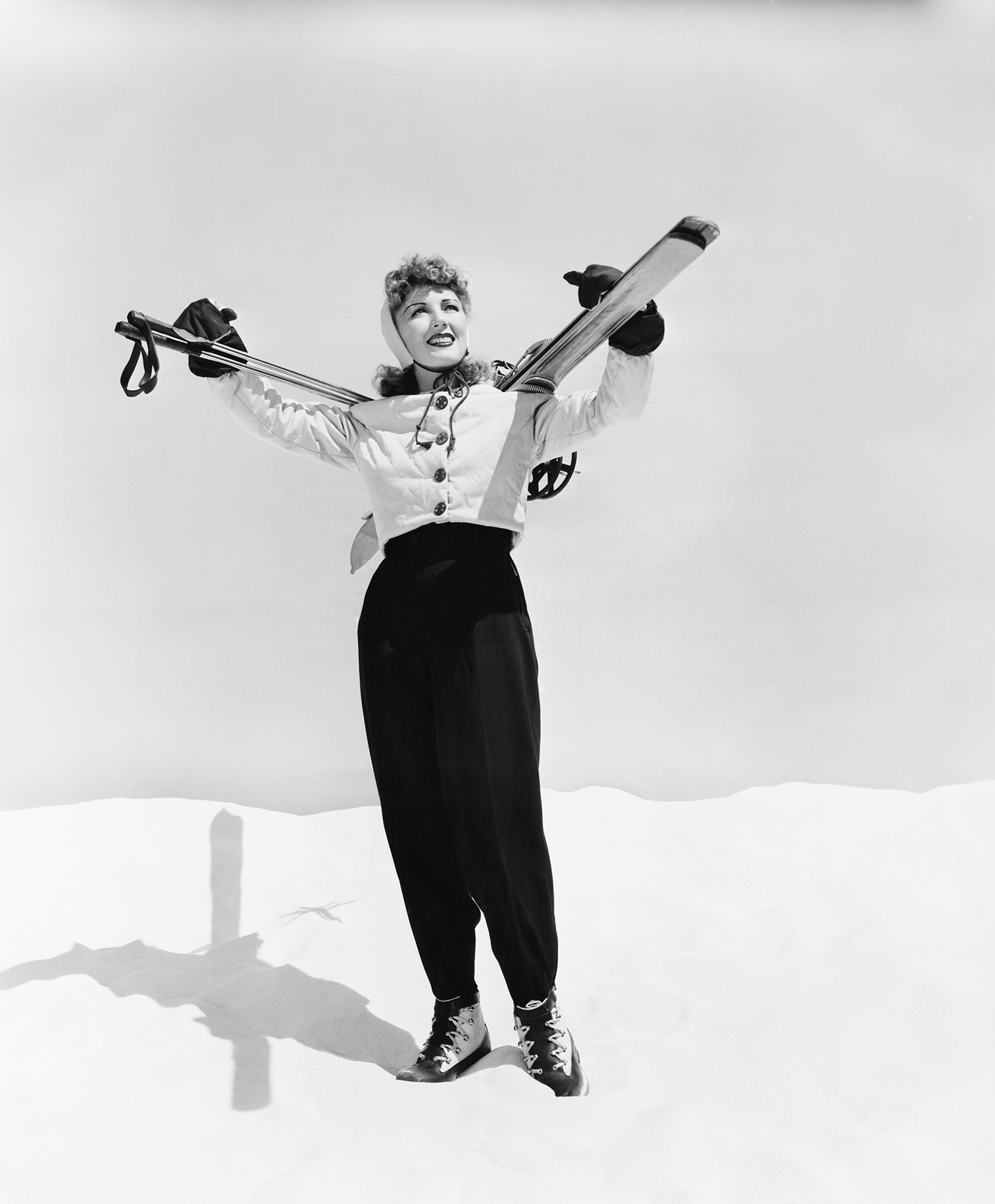 a female skier poses in snow with her skis on her shoulders