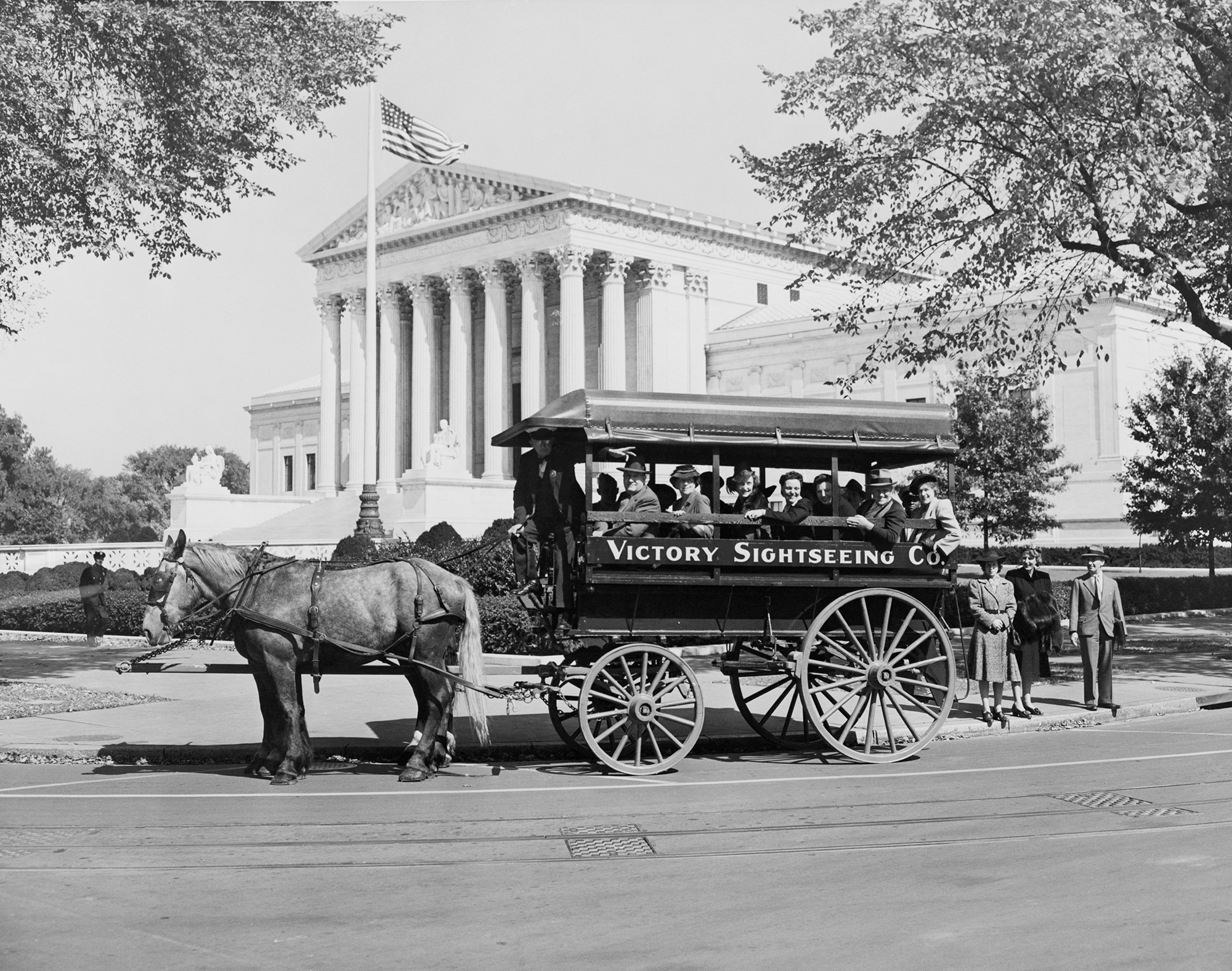 a horse-drawn carriage of tourists drives around washington d.c.