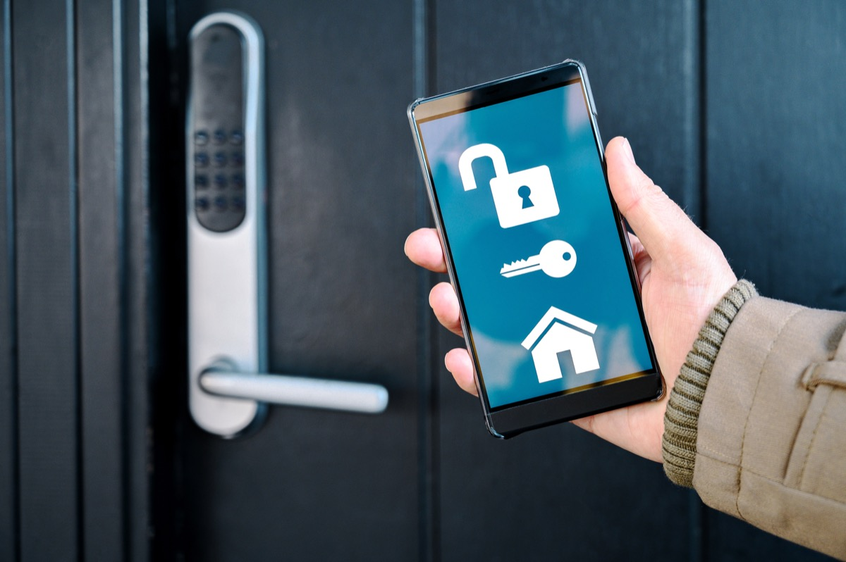 Concept of internet of things integrated in a smart home. Hand holds mobile phone with an app that controls the washing machine and tumble dryer. Could pass as both a home and also a laundromat.