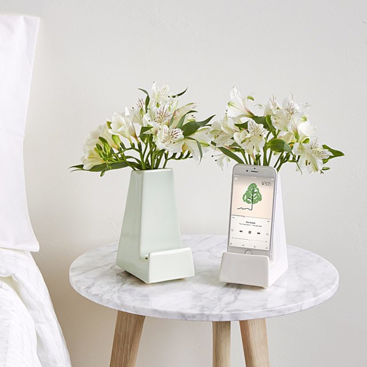 two ceramic vases with flowers and a smartphone on a marble topped nightstand next to a bed