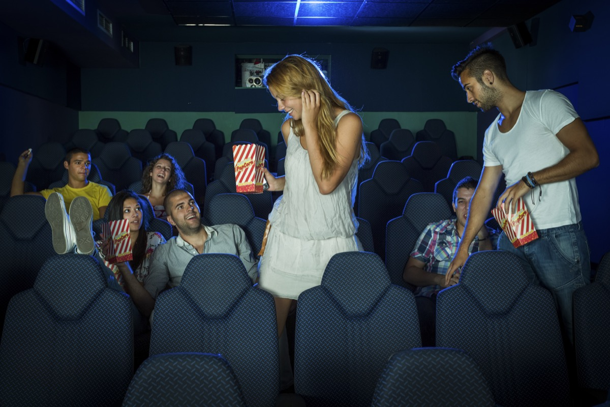 a man and woman holding popcorn squeezing past people sitting down to get to their seats at the movies