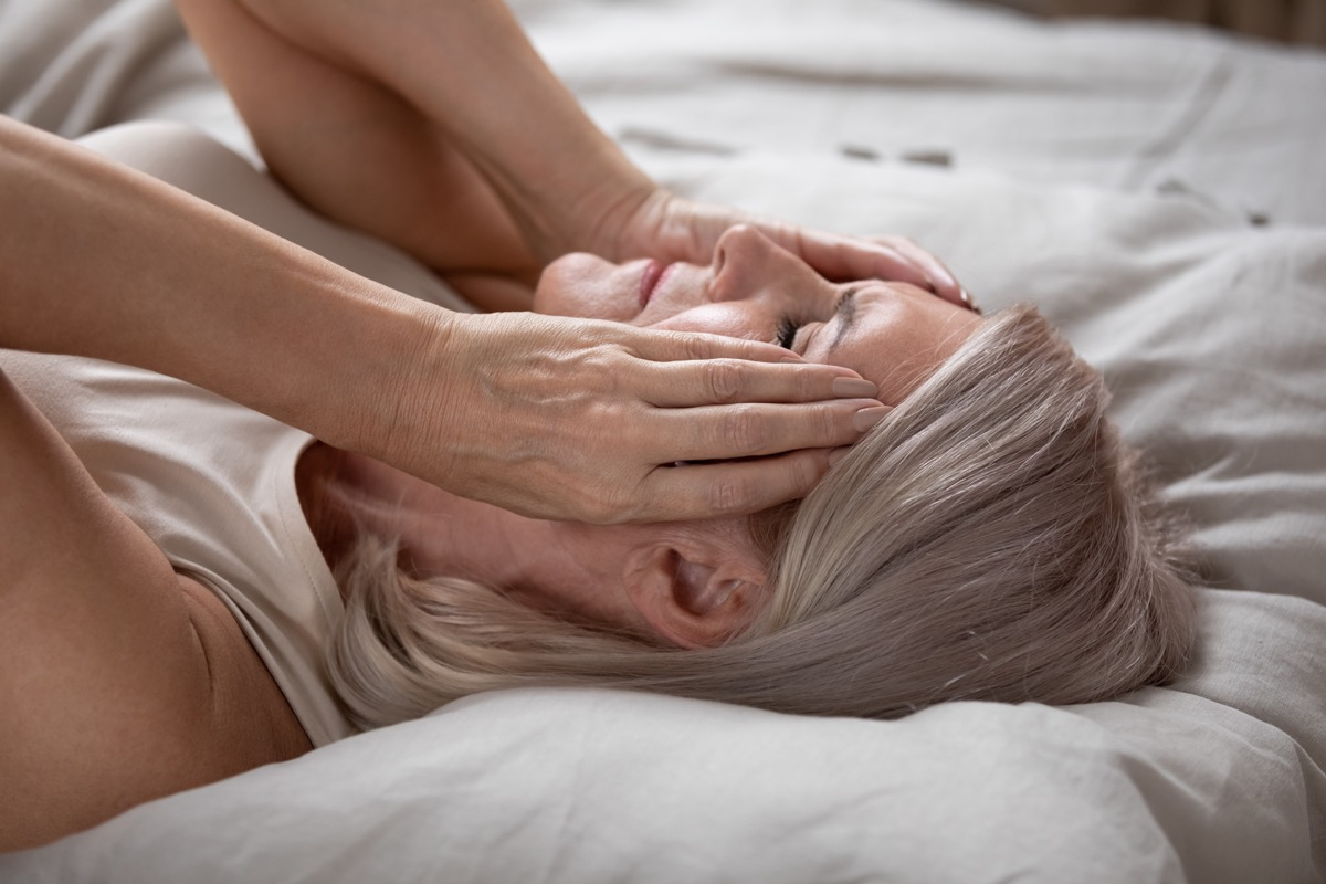 Stressed woman touching her face on the bed