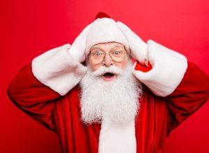 santa standing against red background looking shocked