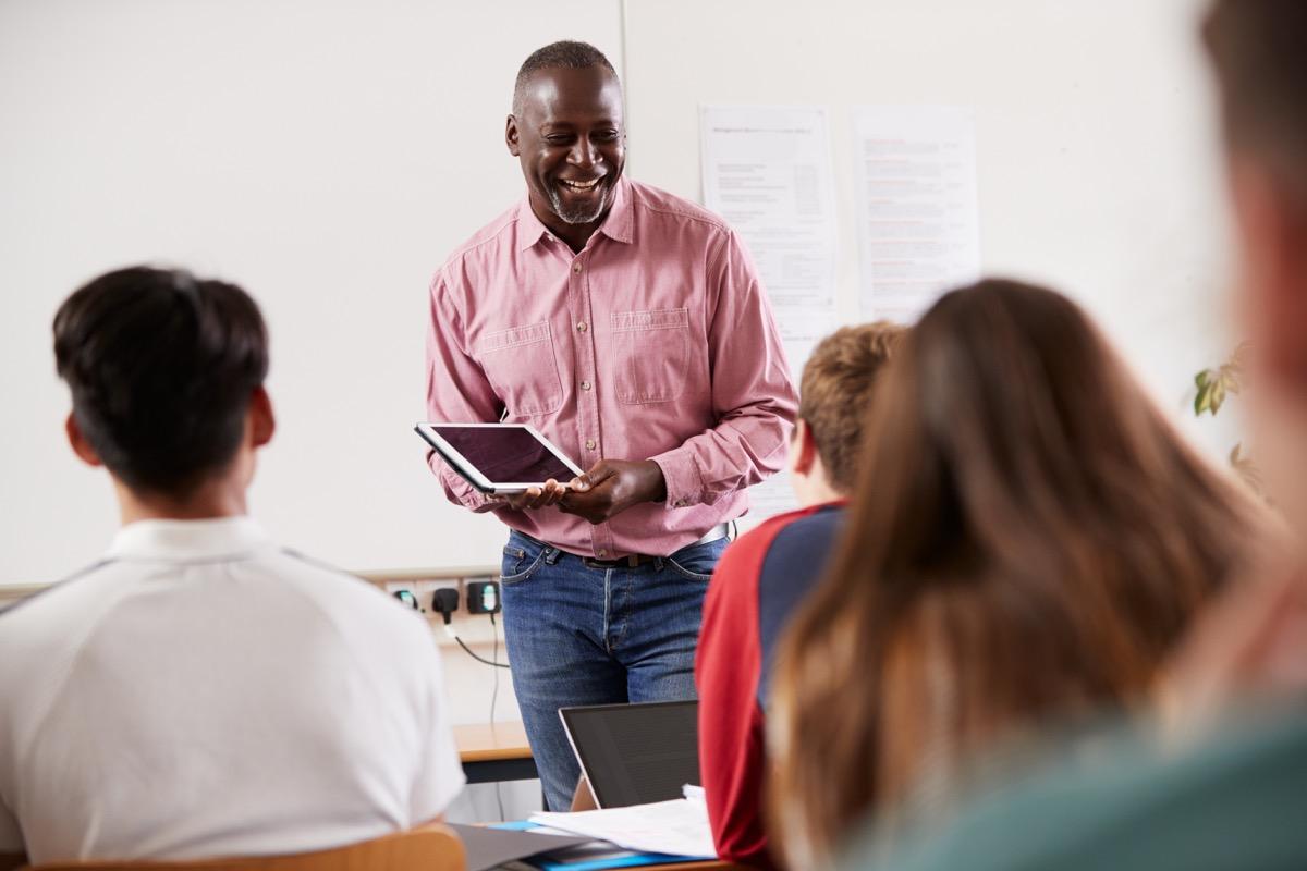 Black teacher smiling and teaching older students