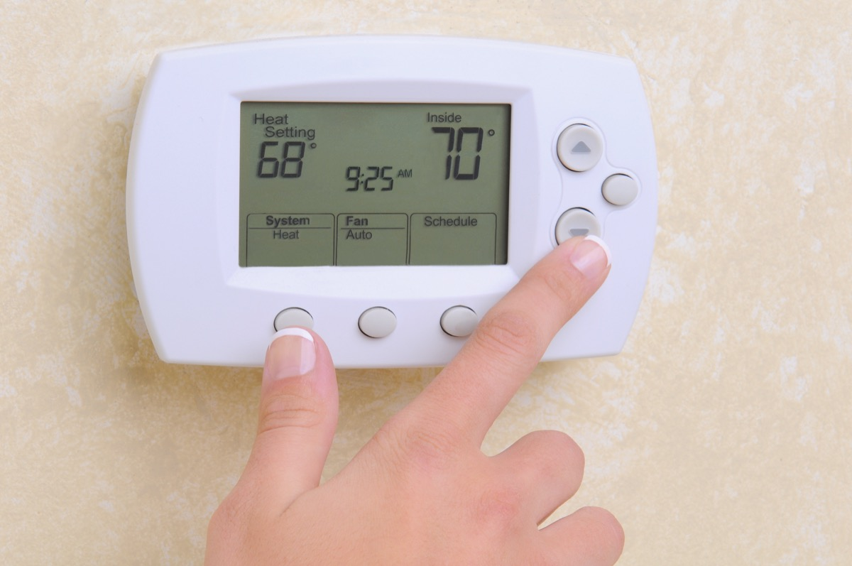 white hand setting thermostat