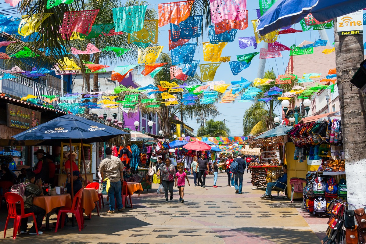colorful flags hang over a pedestrian street with sidewalk tables in tijuana