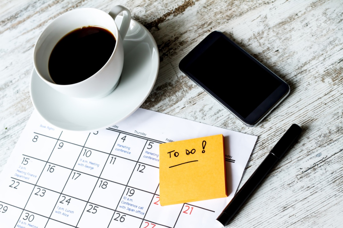to do list on table with post it coffee and phone