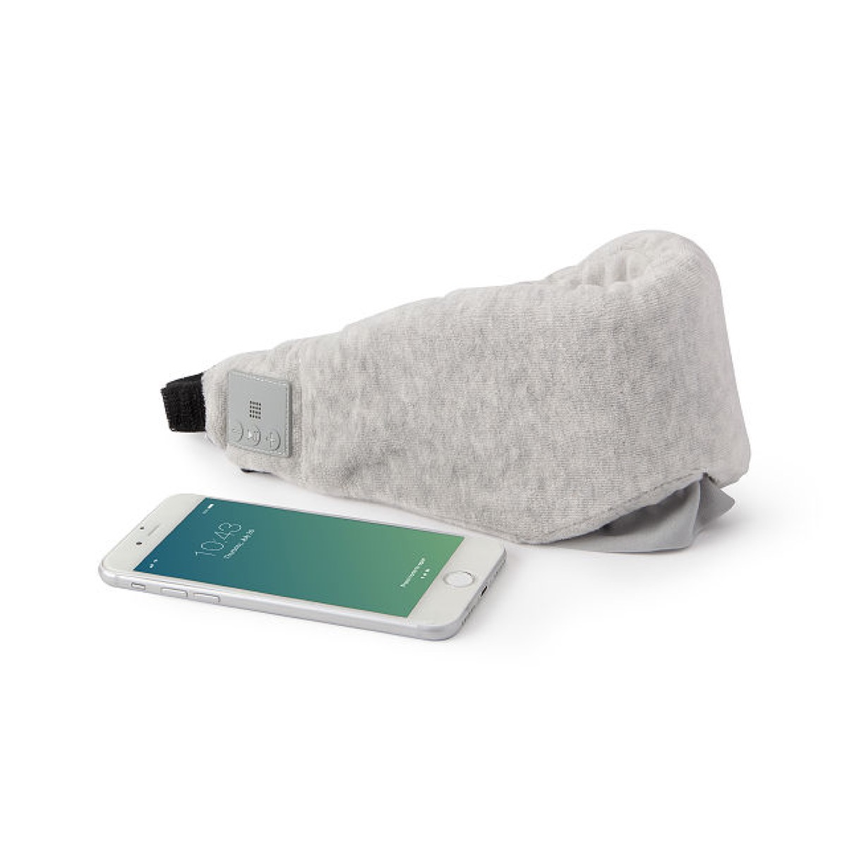 tune out musical sleep mask in gray next to white smartphone
