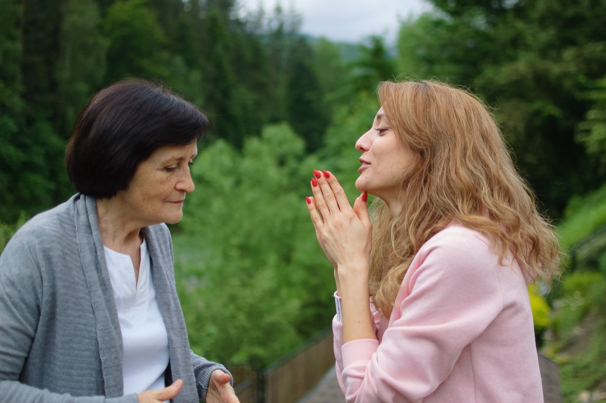 woman apologizing profusely to her mother outside