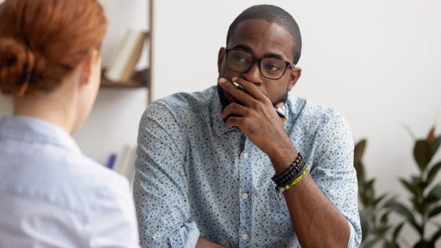 unhappy looking black man having a conversation