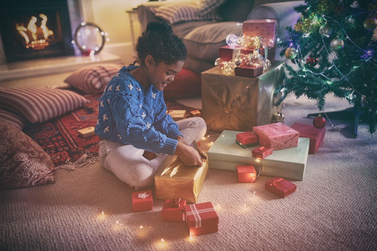 little girl unwrapping gifts in front of the fireplace on christmas morning