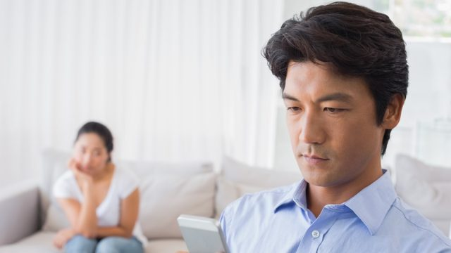 asian man on phone while upset wife looks on from bed