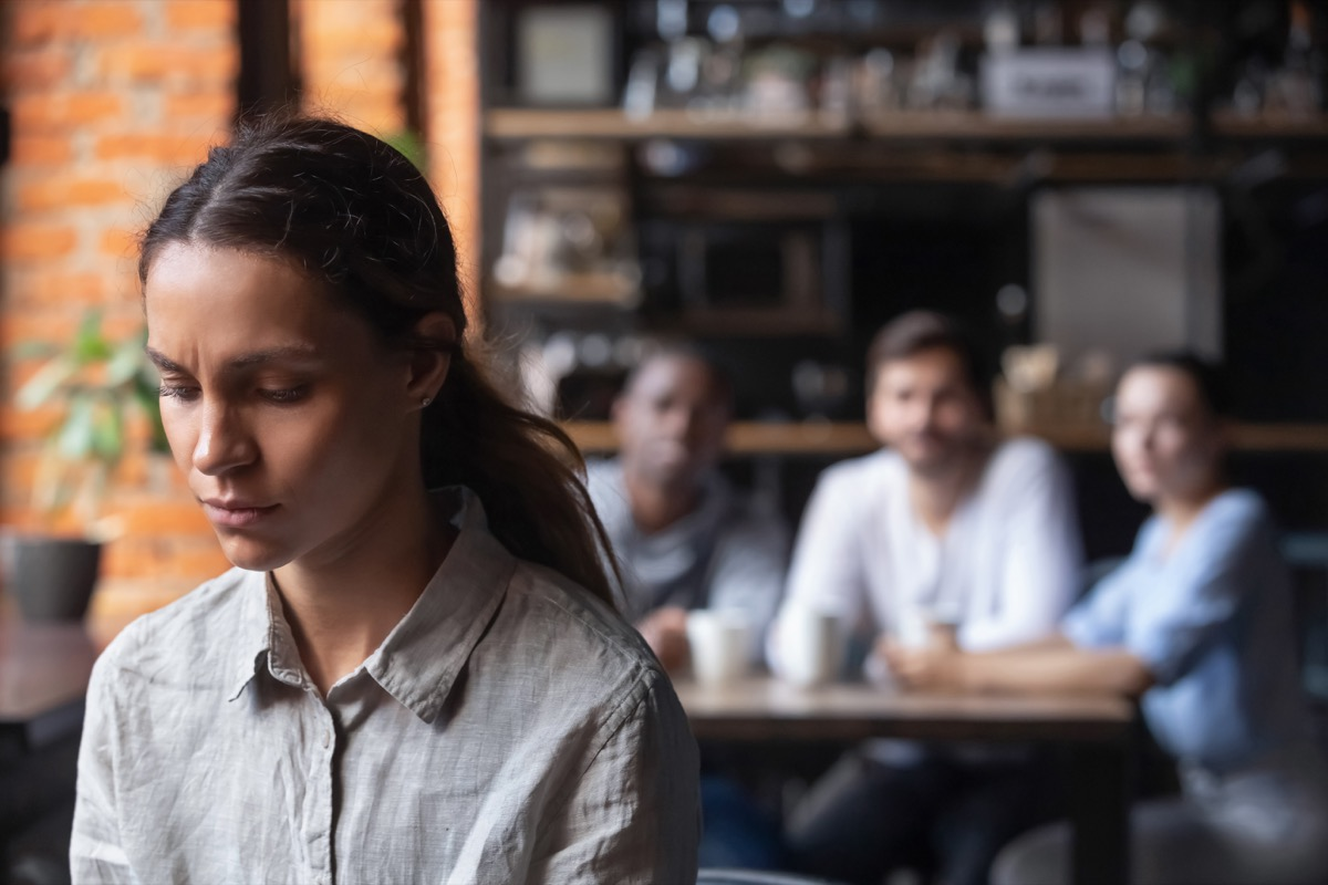 upset woman with three people sitting at a table in the background