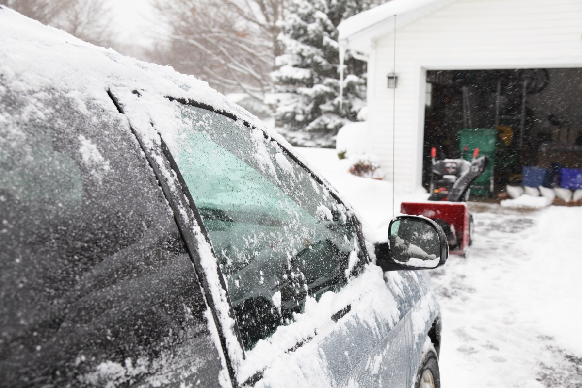 The snowblower in the background has just finished clearing the driveway while the brushed off car in the foreground warms up during a winter storm as heavy snow continues to fall. Selective focus on the car window.