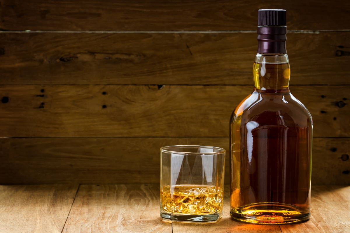 whiskey bottle and glass on wooden table