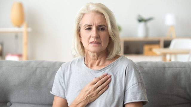 Middle-aged woman clutching her chest in pain on the couch