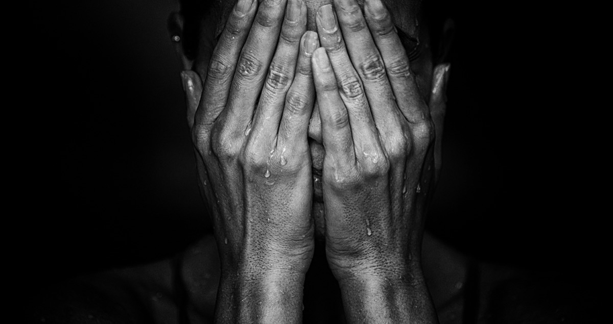 woman crying on black background