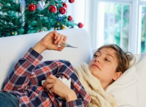Woman sick on the couch on Christmas with a fever potentially from the flu