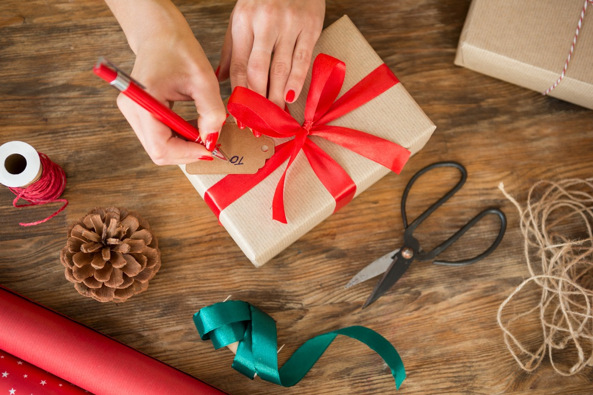 white woman filling out gift tag on christmas present
