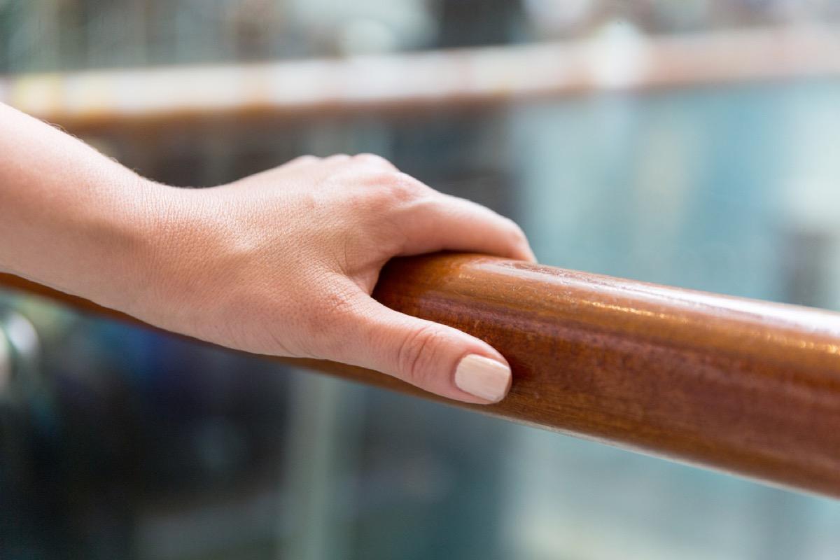white woman holding hand rail