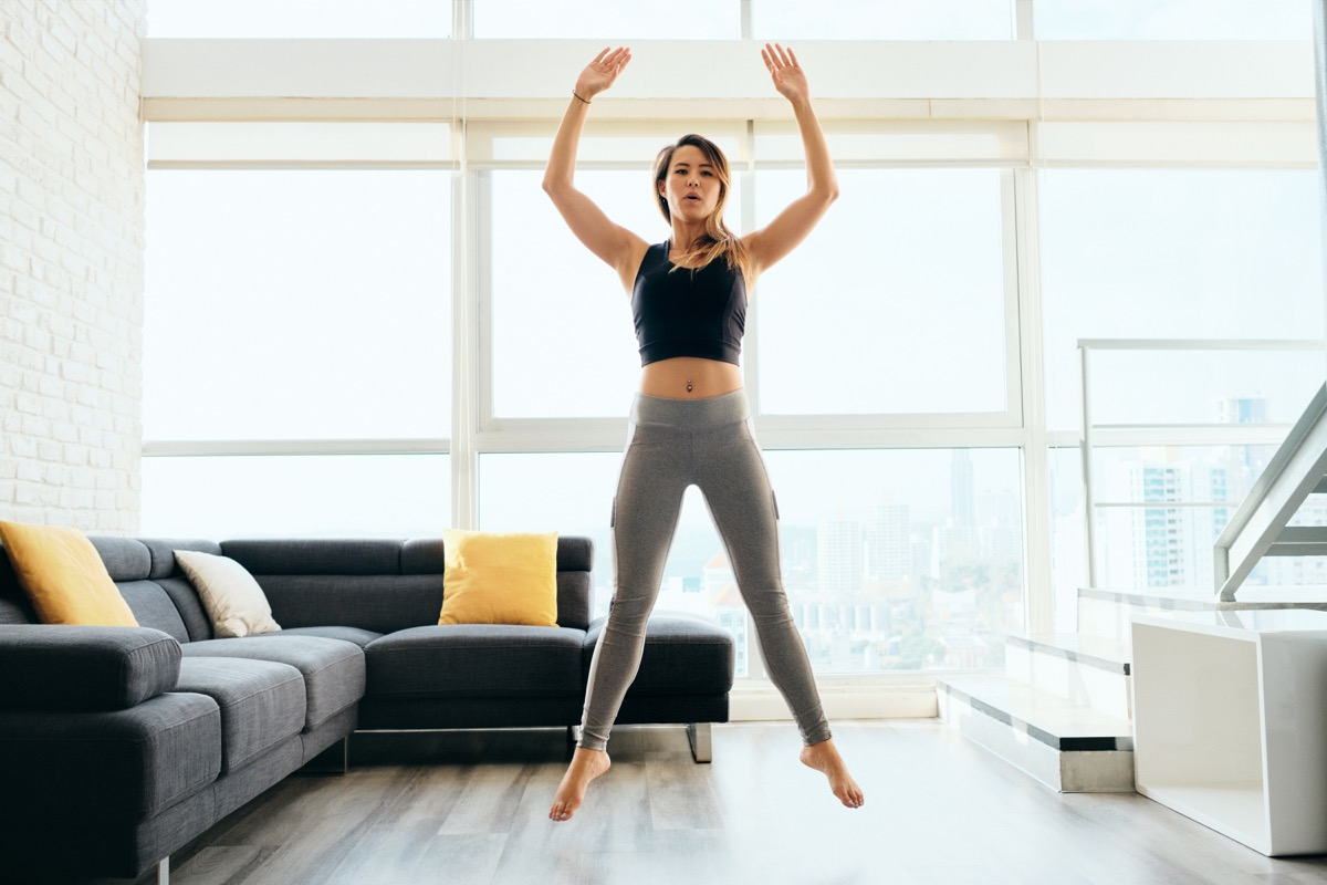 Woman jumping and workout out in the living room