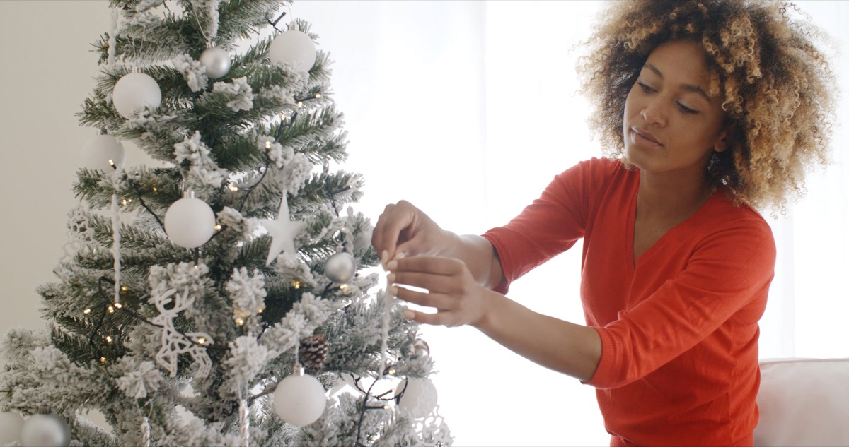 woman looking at the lights on her christmas tree