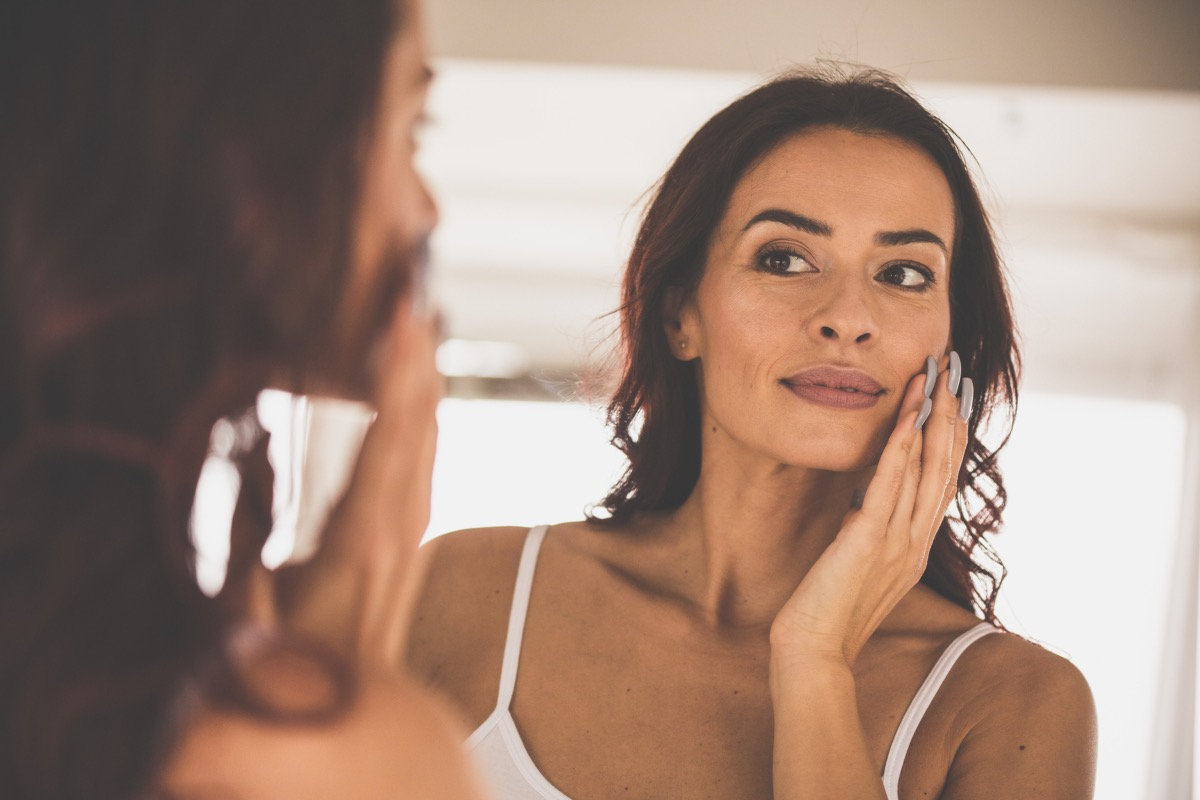 Woman with dry skin moisturizing her face in the mirror