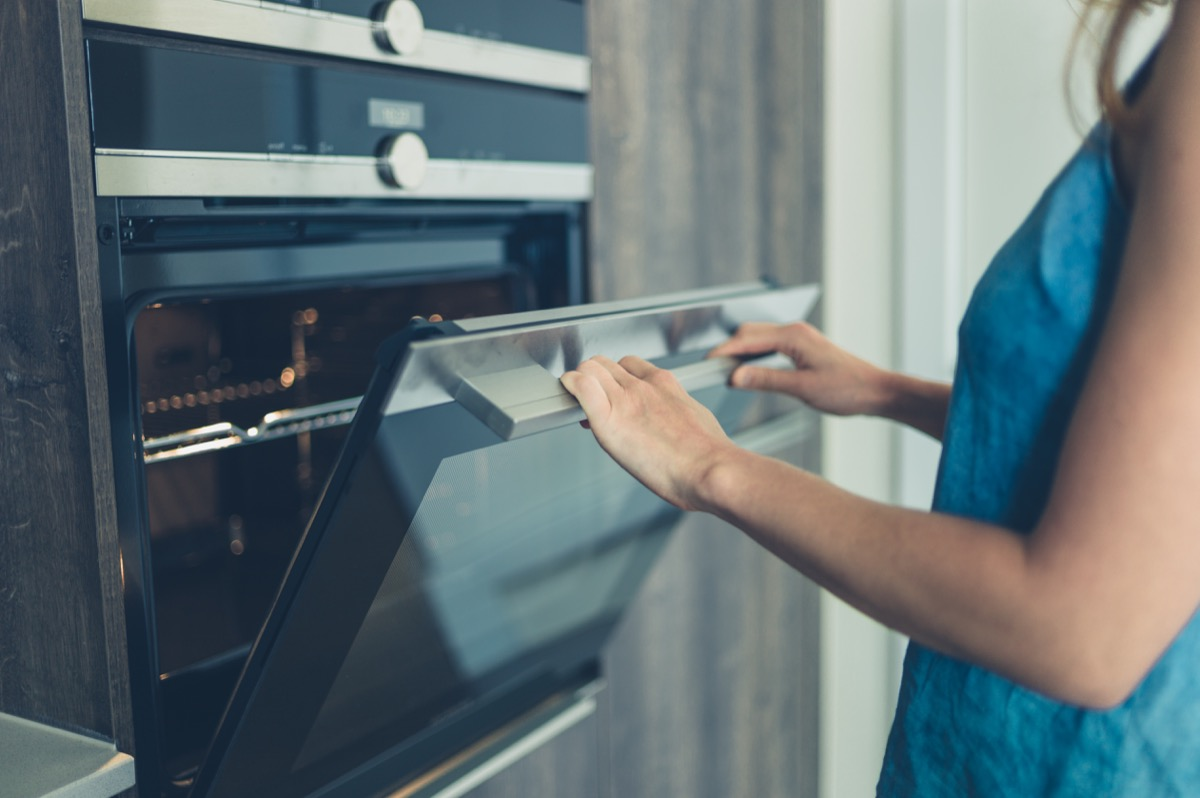 woman opening oven to possible use as a heater