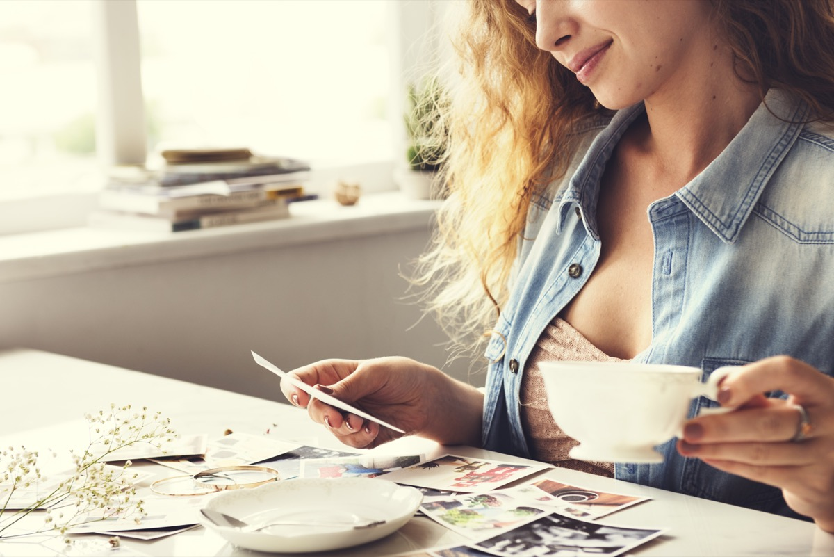 woman reminiscing with old photographs at home