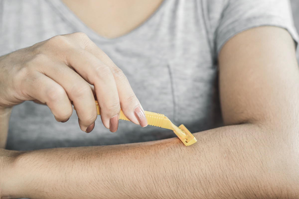 woman shaving her arm air with a razor