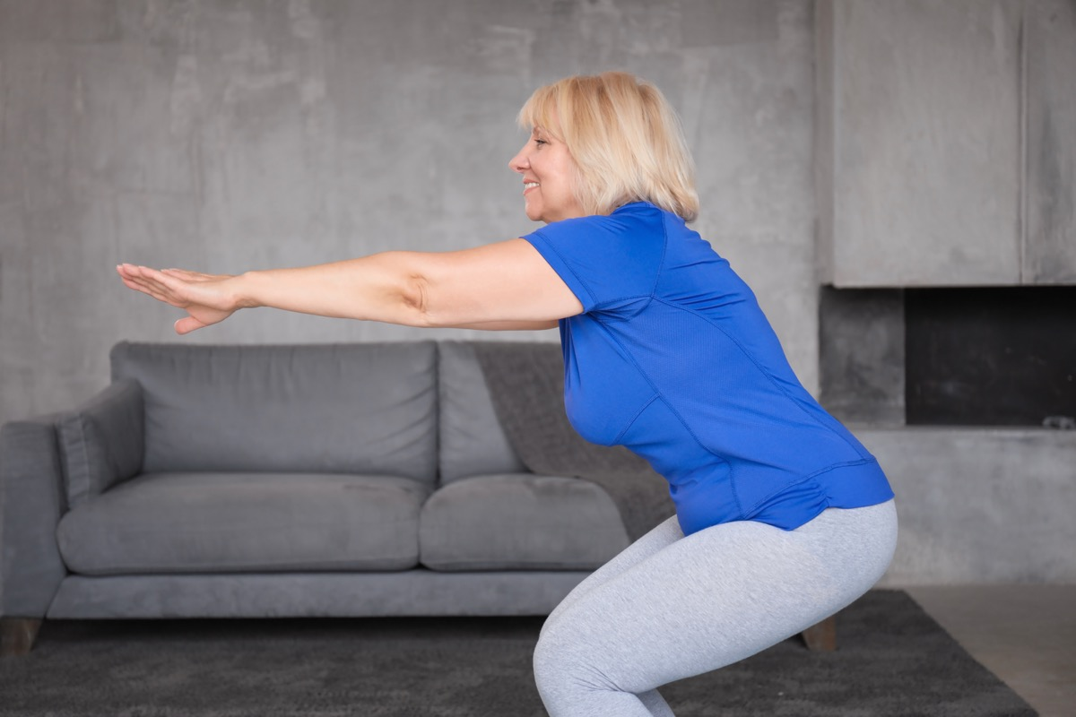 Older woman doing squats in the living room