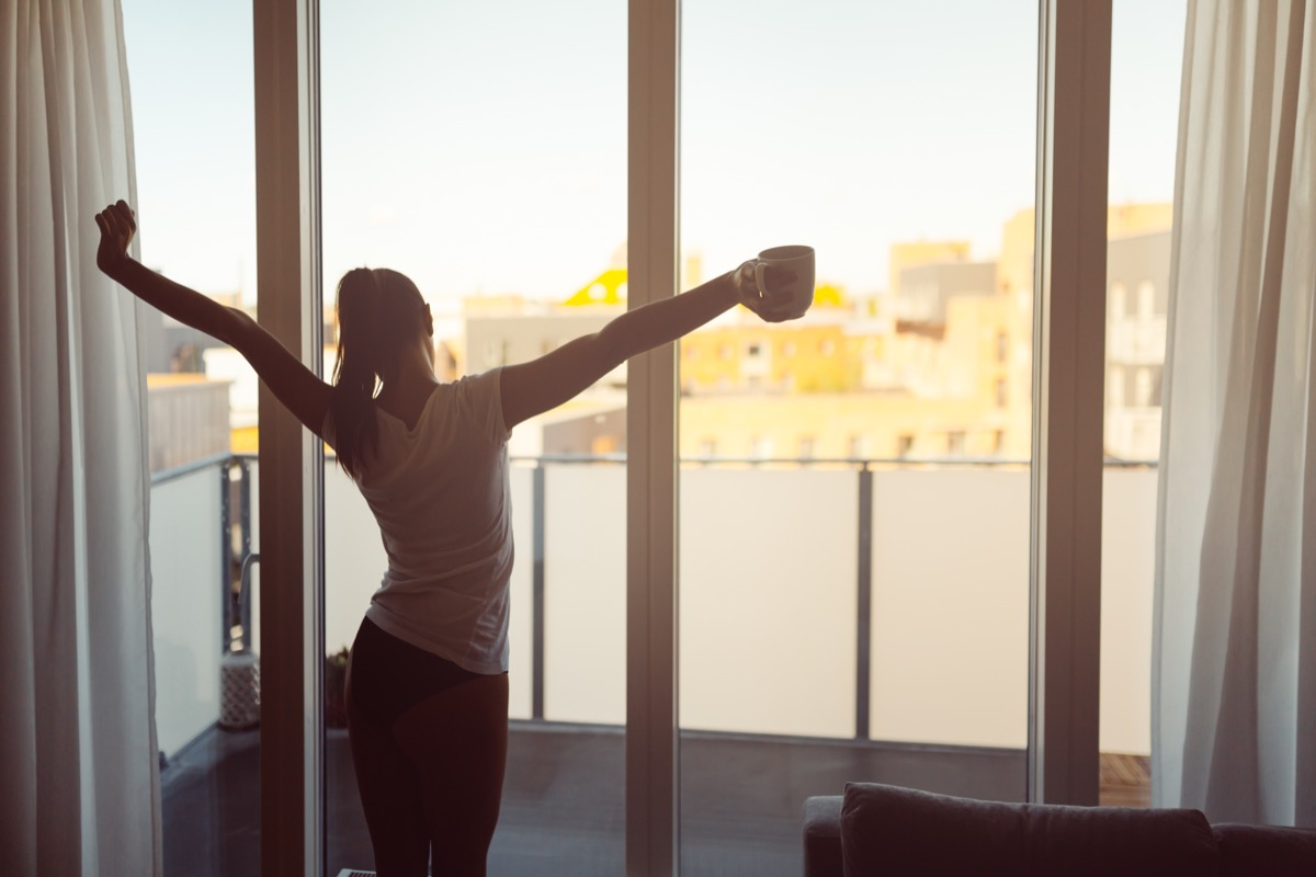 woman stretching in front of window with coffee