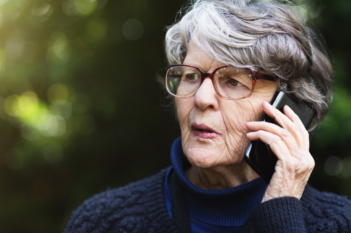 older woman looking anxious as she talks on the phone