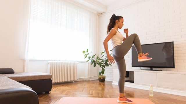 Woman working out and doing some cardio in her living room