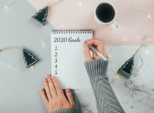 white hand writing down 2020 goals in notebook